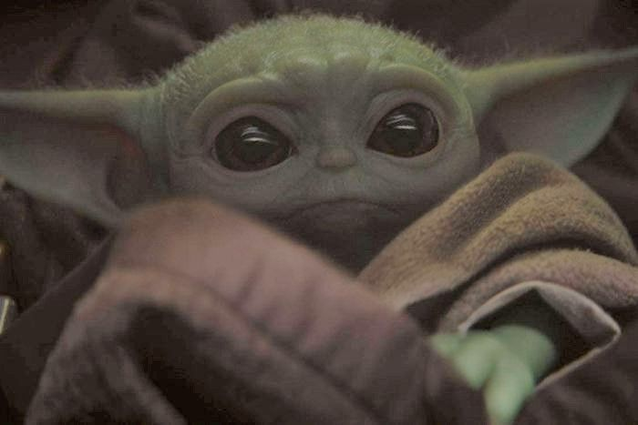 Close up of baby yoda, a green alien with pointy ears and big eyes