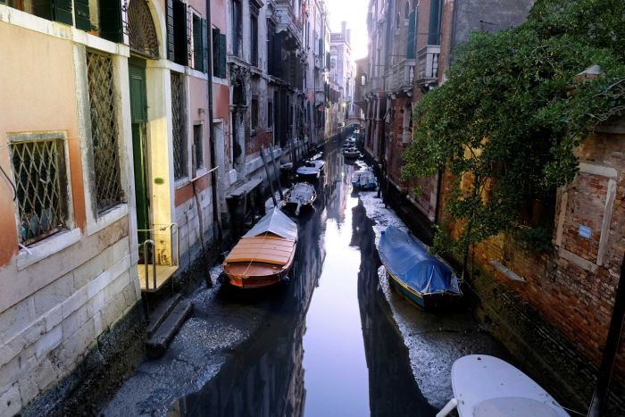 General view of a canal with boats during an exceptional low tide in the city of the Venice lagoon.