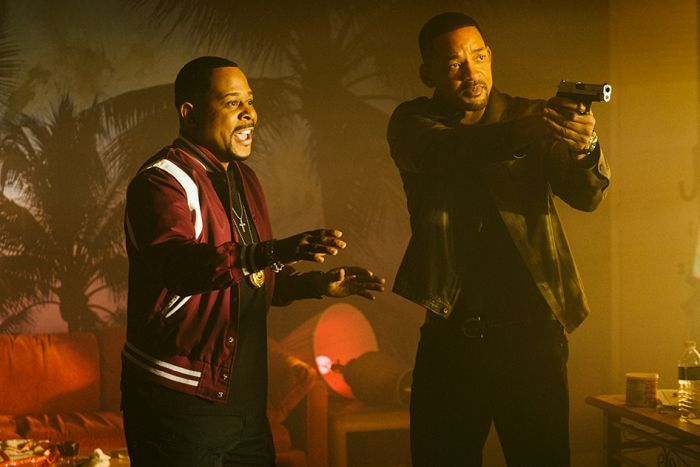 Two men with buzz cuts stand in room, one with gesturing with two hands, the other with raised pistol.