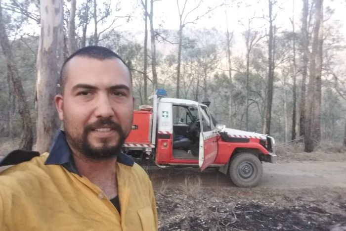A firefighter in uniform takes a photo in front of his truck