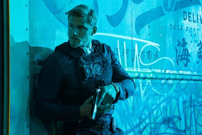 A man wearing bulletproof vest and police attire stands holding pistol against graffitied wall illuminated by light blue light.