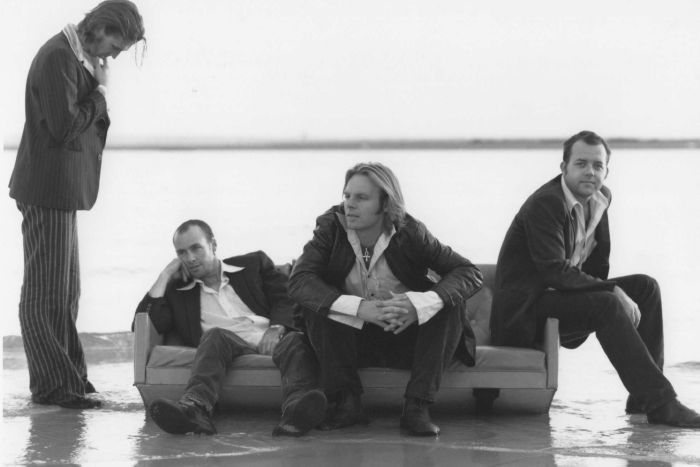 Four men in suits sit on a couch on the beach with water lapping at their feet