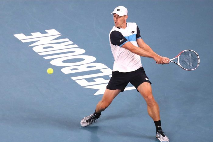 A tennis player has his eyes locked on the ball as he prepares to hit a backhand shot.