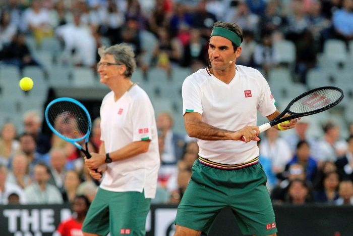 Roger Federer plays a back hand as Bill Gates stands out of focus in the background