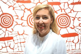 A blonde woman stands smiling in front an Aboriginal painting