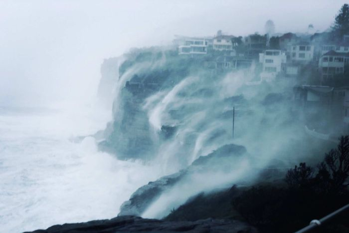 Huge waves and sea spray washes over a group of clifftop homes at Vaucluse in Sydney's east