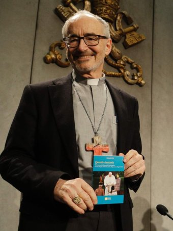 An older man with glasses and Catholic collar smiles and holds a small book.