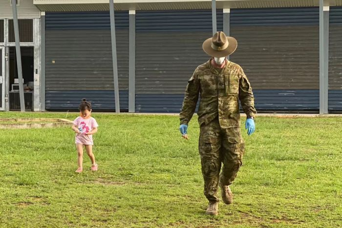 A toddler walks next to a soldier