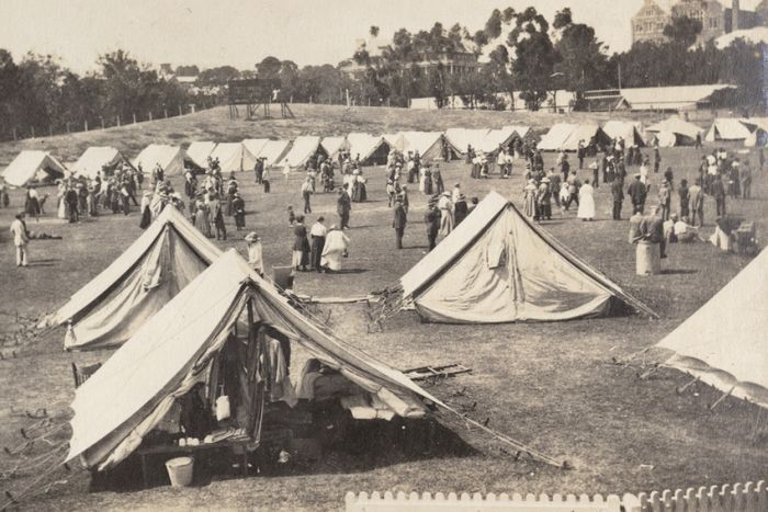 A black and white image of dozens of white tents set up on an oval with people milling about
