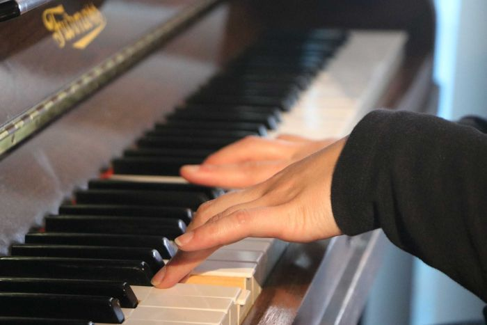A woman's hands while playing a piano.