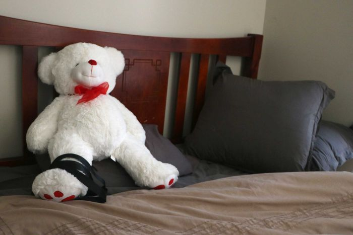 A white teddy bear on a bed.
