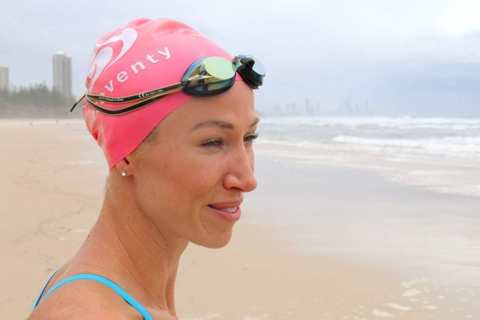 A woman in a swimming cap smiles as she stares at the ocean on a Gold Coast beach