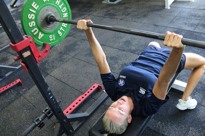 A woman bench pressing weights in a gym