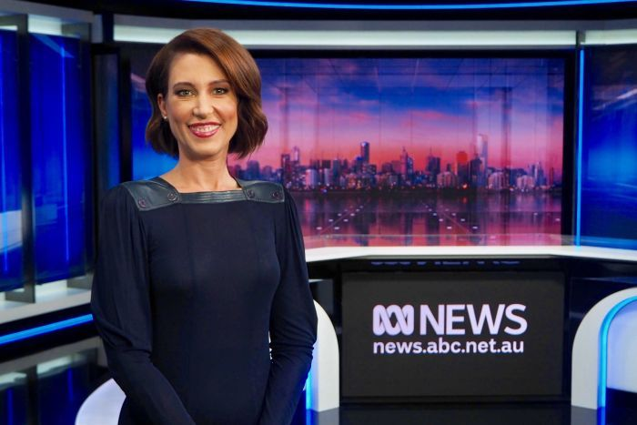 Tamara Oudyn standing in the ABC News studio wearing a navy dress with leather neckline.