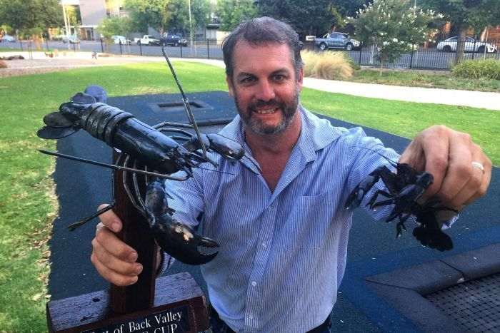 A man holds up a trophy with a fake yabby while holding a real yabby in his other hand.