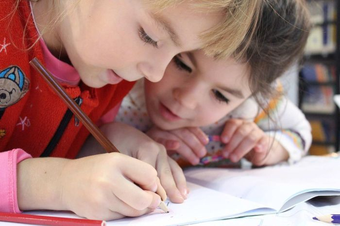 Two kindergarten-aged girls huddled over a pencil and piece of paper. Date unknown