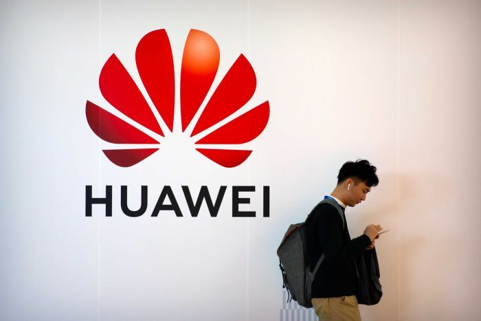 A man on looking down at his phone walks past a Huawei logo