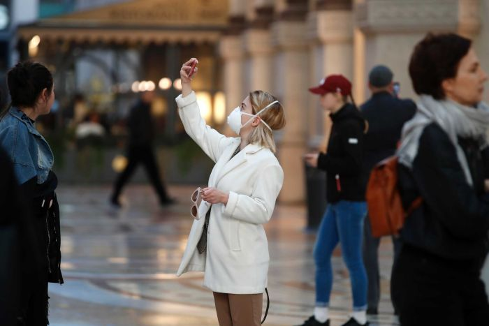 A woman in a white jacket and a medical mask holds up her phone.