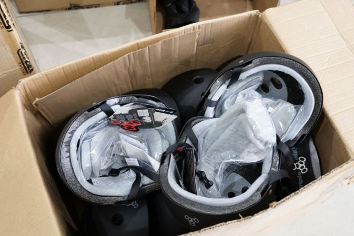 A cardboard box filled with brand new black skating helmets.