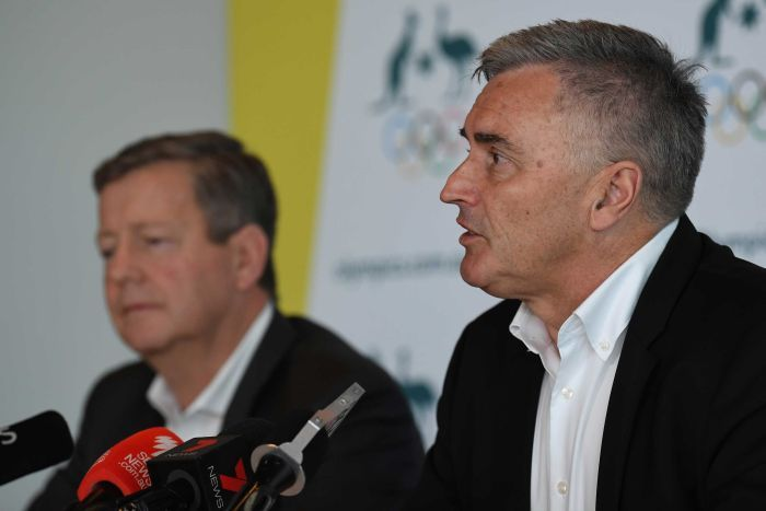 Matt Carroll and Ian Chesterman sit at a press conference wearing white open-necked shirts and black suits