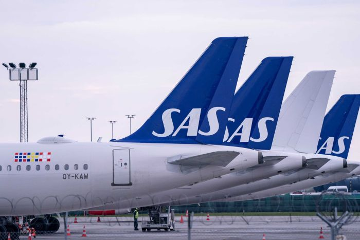 A row of planes with the SAS logo on the queue parked at the airport.