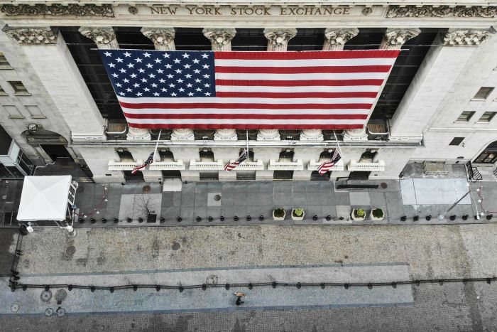 The New York Stock Exchange with large American flag draped on the front and an empty path during the coronavirus block