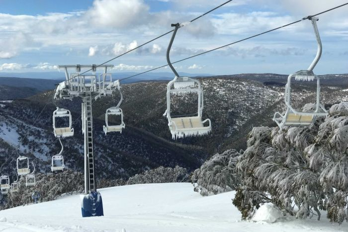 A chairlift over hills scattered with snow. Icicles hang off the chairs on the chairlift.