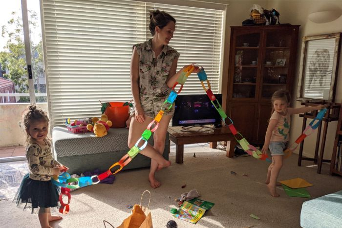 Ed Coper's wife and two daughters hold up a coloured crepe paper chain in a living room