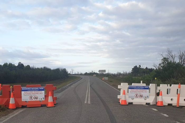 A roadblock stands across a road leading into a national park.