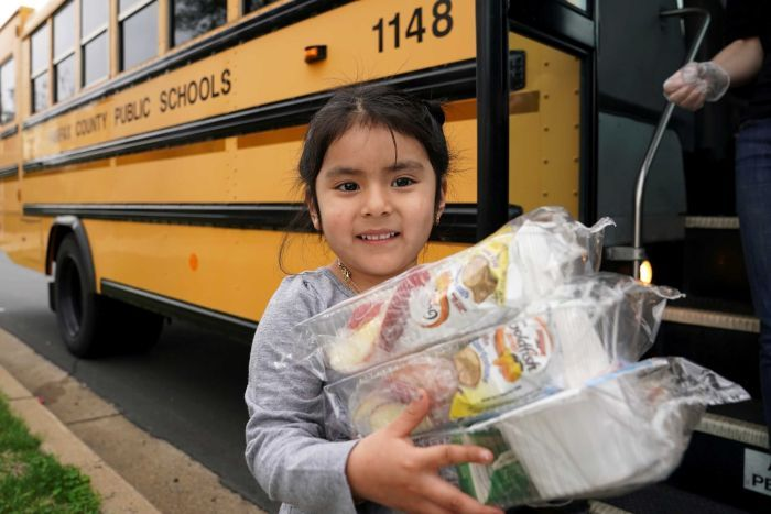 A little girl clutching food next to a school bus