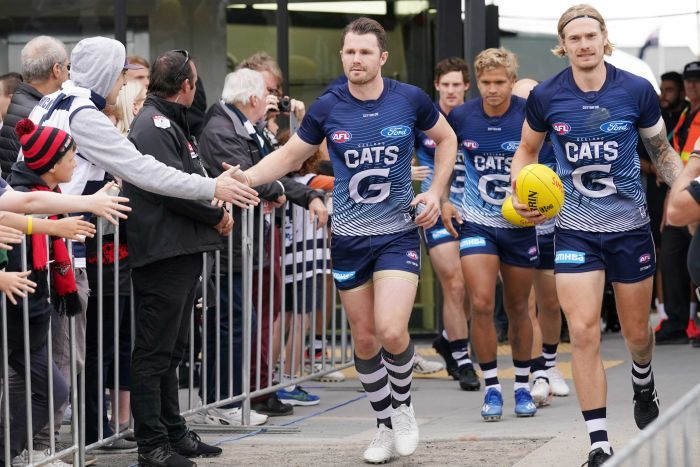 An AFL star runs out slapping hands with fans as he leads his team out before a pre-season game.