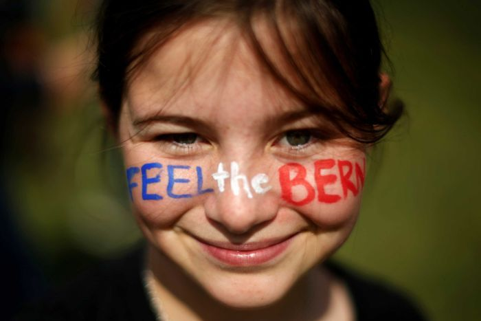 A young girl with Feel The Bern written on her face