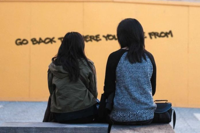 A mother and child sit while looking at a wall that reads