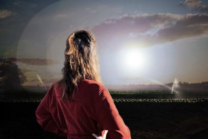 A woman stares out to look at a field (edited image).