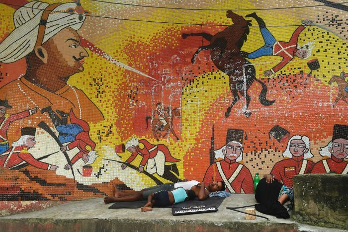 A family sleeps in front of a mural showing Tipu Sultan. It also shows British soldiers being injured.