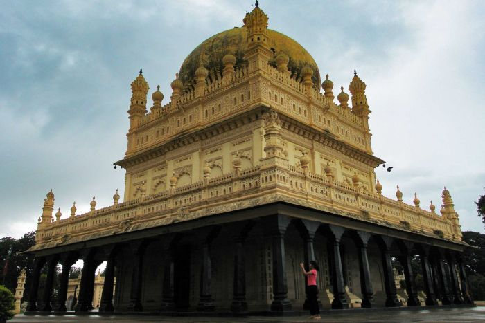 An ornate cream and black coloured mausoleum, several stories high.