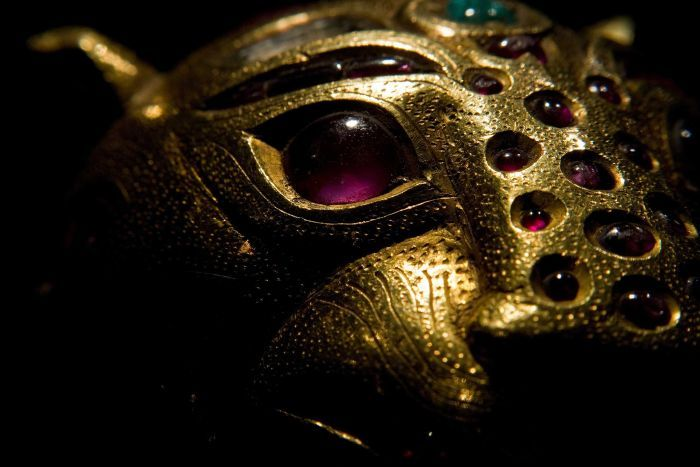 A close up of the face of a gold tiger. Its eyes, stripes and other details are purple gems.