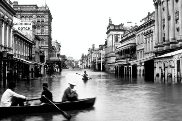Historic photo of Brisbane's Queen Street after the 1893 show people passing through the street in row boats.