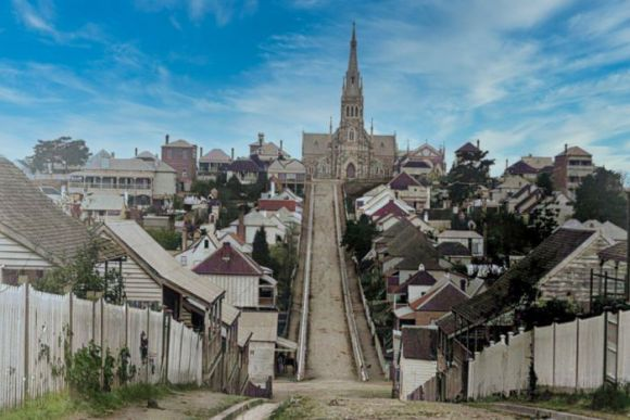 A large church sits at the top of a hill. There are rows of houses along the hill.