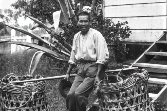 A man leans on a large basket outside of a house.