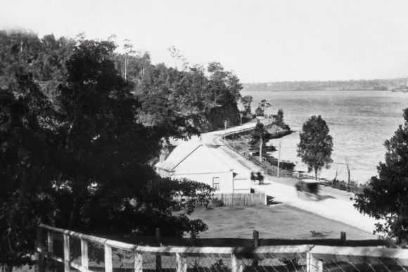 A road that runs along the Brisbane River and wraps around a curve of a hill.