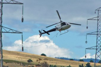 A helicopter helps string a power line between transmission towers in central Tasmania.