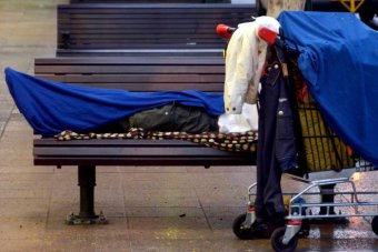 A homeless person lies on a seat.