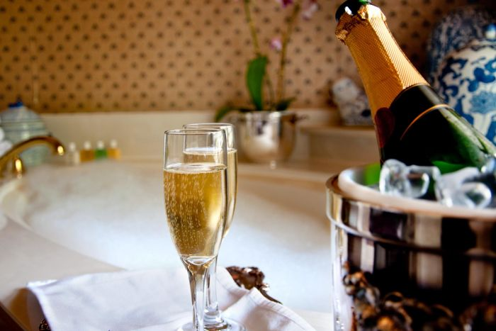 Glasses of champagne sit next to an bottle.