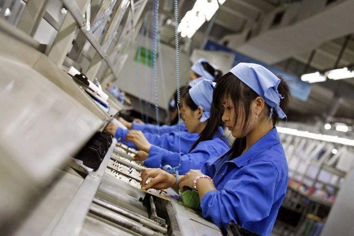 Chinese workers in blue jumpsuits place conductors on electric circuit boards in a line.