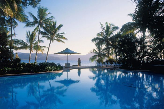 A couple overlooking a pool at Daydream Island's resort in the Whitsundays in north Queensland.