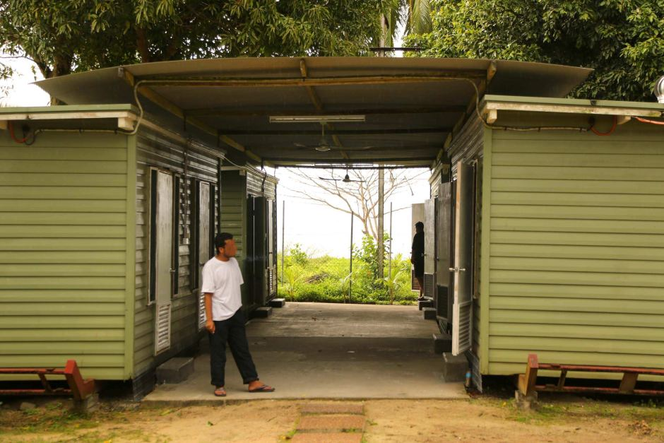 A man stands outside a demountable building on Manus Island