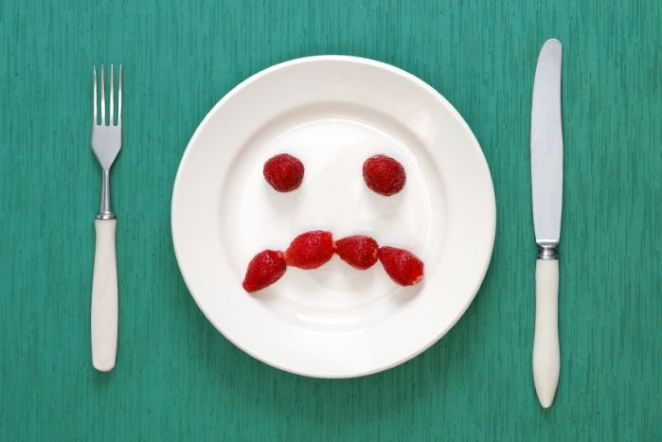 A plate with a sad face made out of berries.