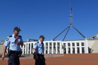Two police officers walk past the front of Canberra Parliament House. The sky is bright blue.