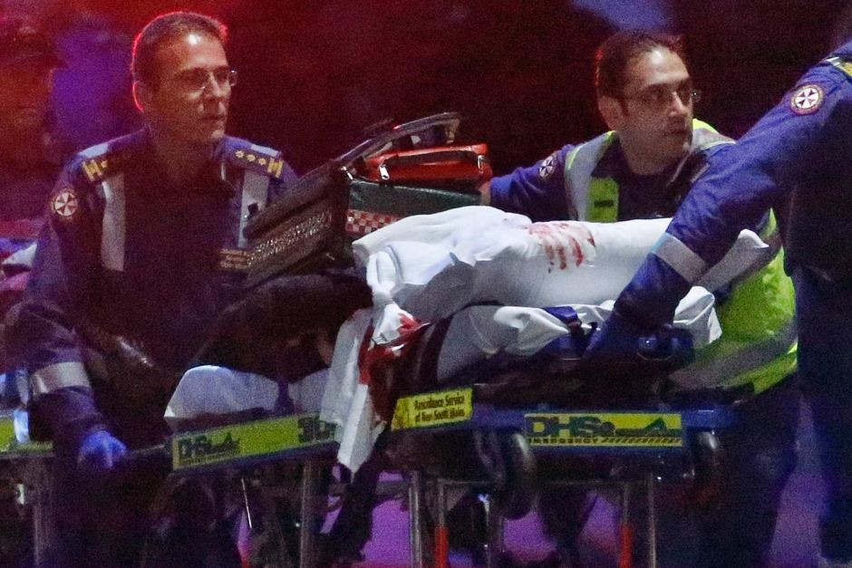 Paramedics remove a person, with bloodstains on the blankets covering the person, on a stretcher after the end of the Sydney siege on December 16, 2014.